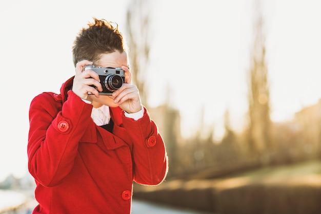 Mädchen, das fotos auf der ufergegend bei sonnenuntergang macht
