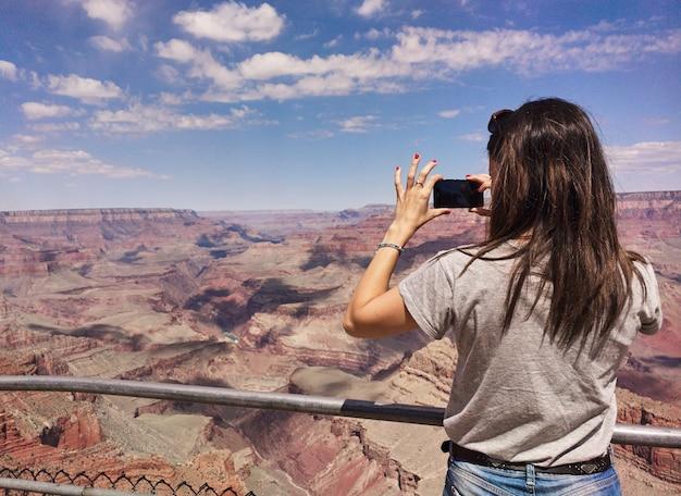 Mädchen, das fotos im grand canyon mit handy macht.