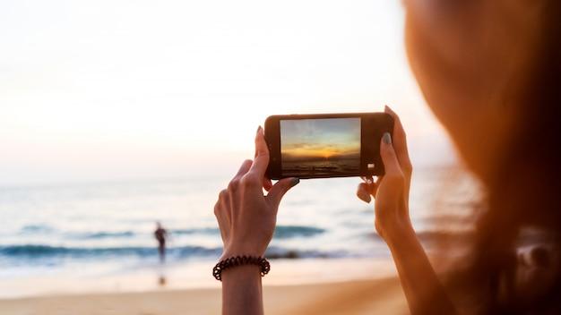 Mädchen, das fotos mit ihrem telefon des sonnenuntergangs oder des sonnenaufgangs am strand macht
