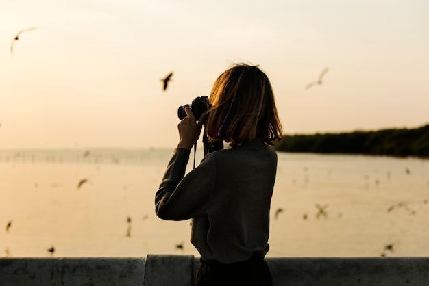 Mädchen, das fotos von den vögeln macht, die über den ozean fliegen