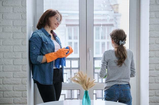 Mädchen, das frau hilft, fenster zu waschen