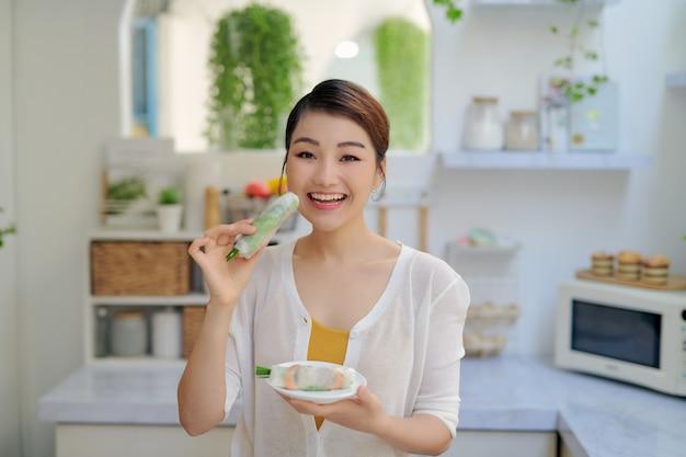 Mädchen, das frische frühlingsrollen mit garnelen isst