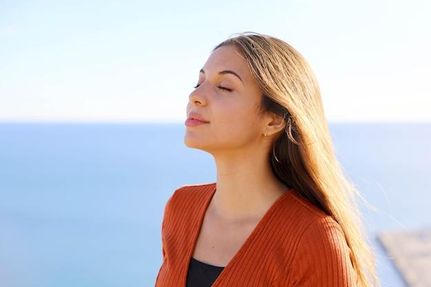 Mädchen, das frische luft mit blauem meer atmet