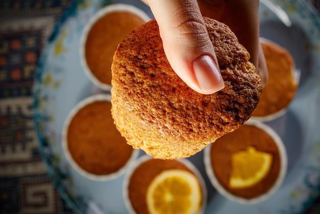 Mädchen, das frischen kleinen kuchen in ihrer hand hält.