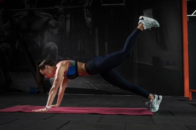 Mädchen, das frontplank auf geraden armen mit beinheben im fitnessstudio durchführt