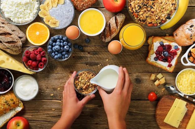 Mädchen, das frühstück - granola mit joghurt, früchten, beeren, milch, joghurt, saft, käse kocht. sauberes essen, diät, entgiftung, vegetarisches lebensmittelkonzept