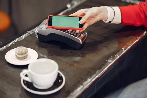 Mädchen, das für ihren latte mit einem smartphone durch kontaktlose pay pass-technologie bezahlt