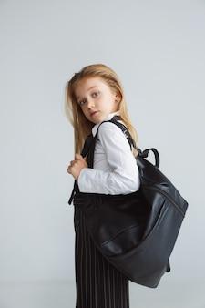 Mädchen, das für schule nach einer langen sommerpause vorbereitet. zurück zur schule. kleines weibliches kaukasisches modell, das in der schuluniform mit rucksack auf weißer wand aufwirft. konzept für kindheit, bildung, urlaub.