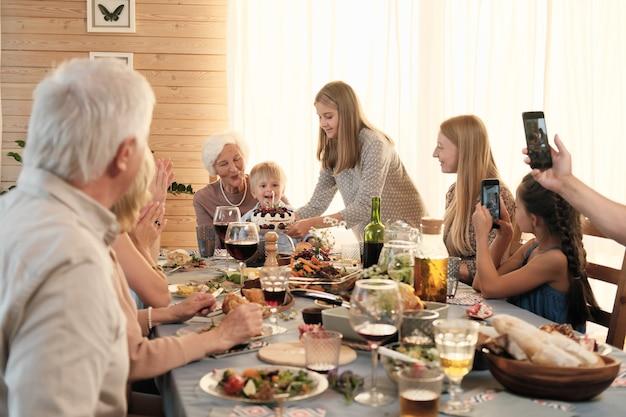 Mädchen, das geburtstagstorte auf den tisch legt, während geburtstag mit ihrer großen familie zu hause feiert