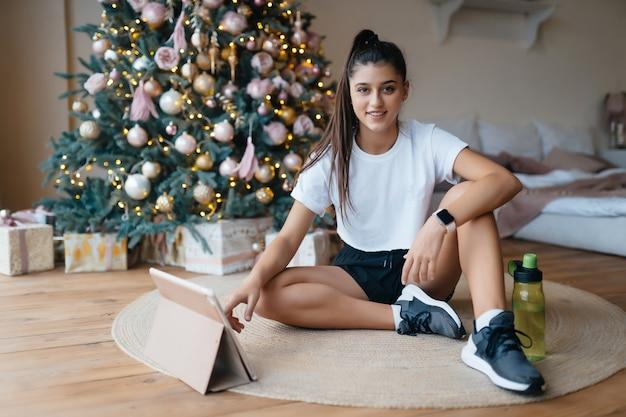 Mädchen, das gegen den hintergrund der weihnachtsdekoration aufwirft. weihnachten online-urlaub.