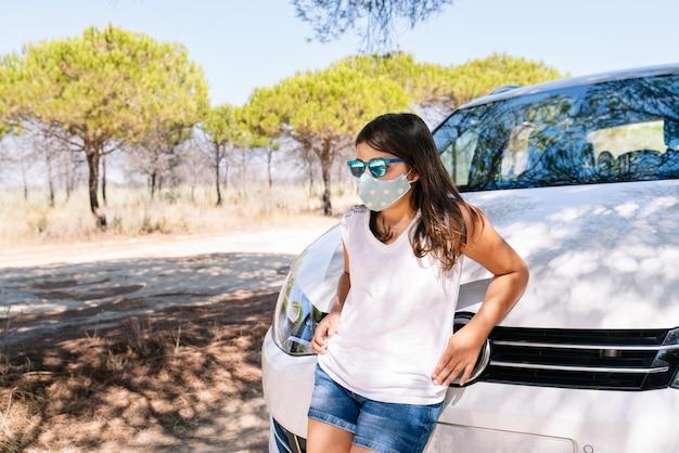 Mädchen, das gegen die motorhaube eines autos mit einer gesichtsmaske an einem urlaubsstopp auf einer kiefernwaldstraße in der covid19-coronavirus-pandemie lehnt