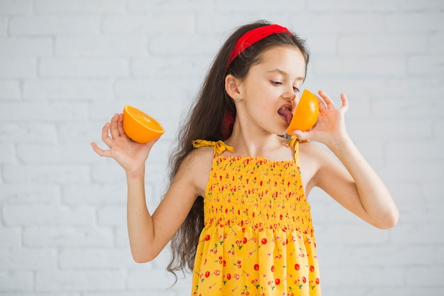 Mädchen, das gegen die weiße backsteinmauer leckt orangen steht