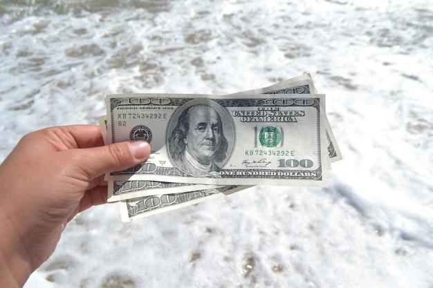 Mädchen, das geldschein von 300 dollar auf dem hintergrund der meere hält