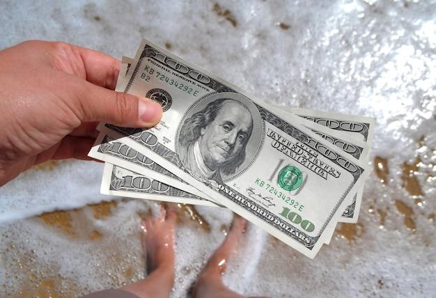 Mädchen, das geldschein von 300 dollar auf dem hintergrund der meereswellen hält