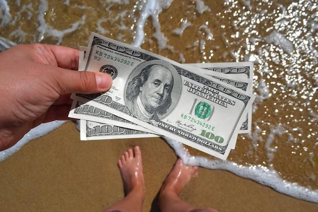 Mädchen, das geldschein von 300 dollar auf dem hintergrund des seeozeans hält