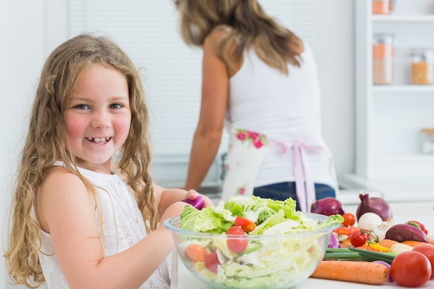 Mädchen, das gemüsesalat zubereitet