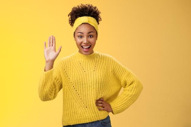 Mädchen, das gerne die hand hebt, bereit ist, kandidat zu sein, sagt hallo, winkende palmengrußgeste, die allgemein lächelt, sich glücklich fühlt und gerne freunde begrüßt, die party in der nähe der tür auf gelbem hintergrund einladen.