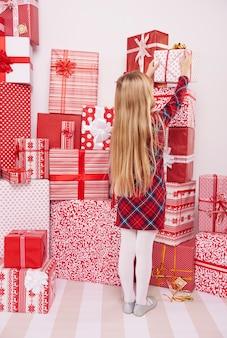 Mädchen, das geschenk vom stapel nimmt