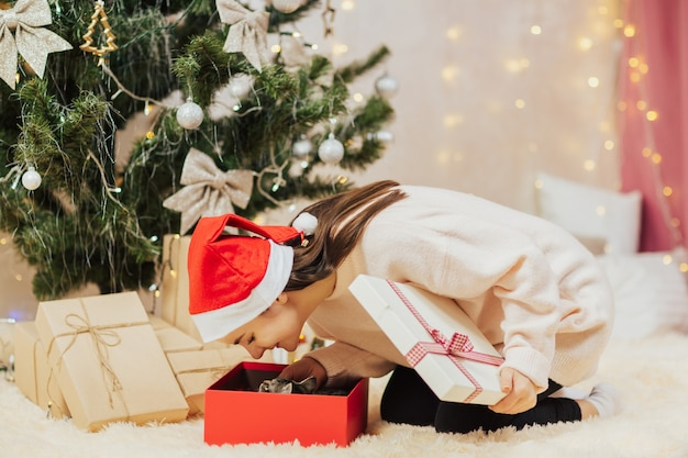 Mädchen, das geschenkbox mit kätzchen öffnet.