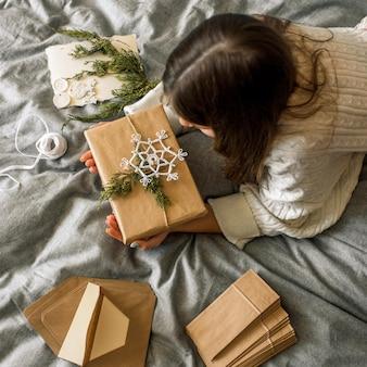 Mädchen, das geschenke mit weihnachtsdekoration einwickelt