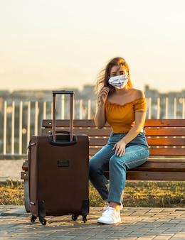 Mädchen, das gesichtsmaske mit koffer im park trägt. reisen während der pandemie