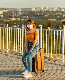 Mädchen, das gesichtsmaske trägt, während auf koffer im park sitzt. reisen während der pandemie