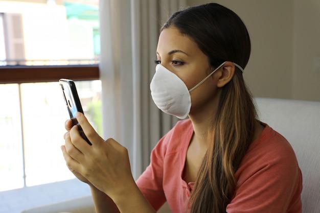 Mädchen, das gesichtsmaske unter verwendung des mobiltelefons liest, das informationen über coronavirus-krankheit 2019 zu hause liest.