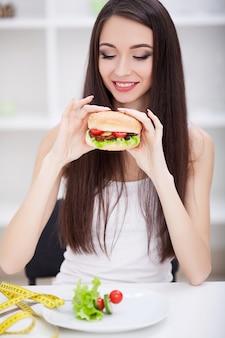 Mädchen, das gesundes gegen ungesunde fertigkost wählt