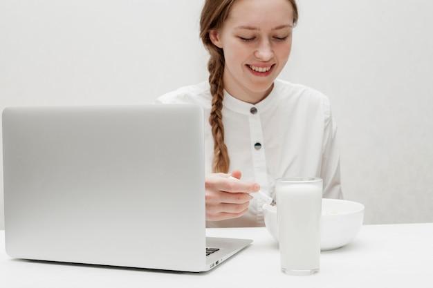 Mädchen, das getreide mit milch auf ihrem schreibtisch isst
