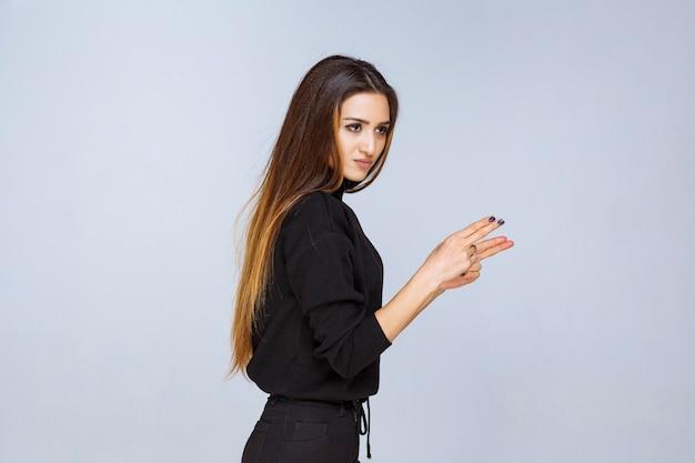 Mädchen, das gewehrzeichen in der hand zeigt. foto in hoher qualität
