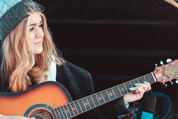 Mädchen, das gitarre spielt, das auf dem kofferraum des autos im winterwald sitzt - reisen mit dem auto