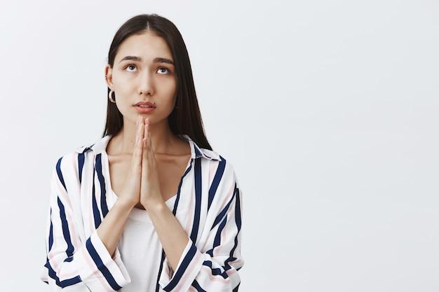 Mädchen, das gott betet und um gnade und glück bittet. porträt einer fokussierten gutaussehenden jungen frau in gestreifter bluse, händchen haltend im gebet, mit verträumtem ausdruck aufblickend, hoffend, gläubig