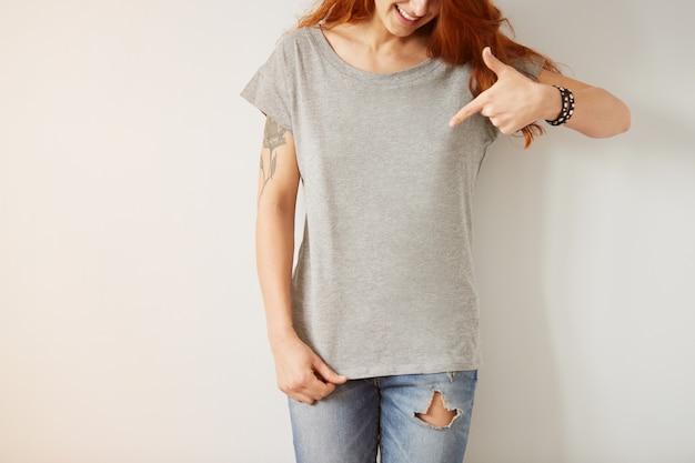Mädchen, das graues leeres t-shirt trägt, das auf weißer wand steht