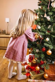 Mädchen, das großen weihnachtsbaum verziert