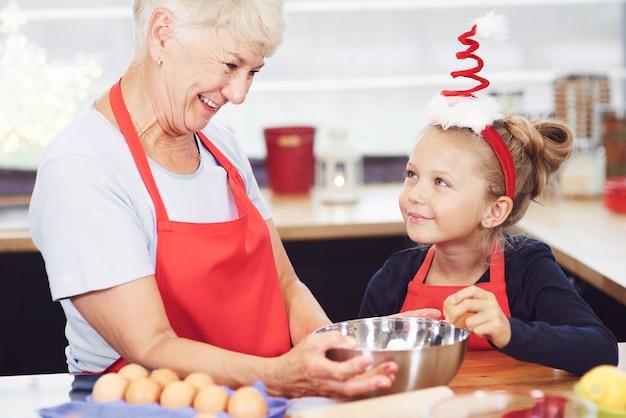 Mädchen, das großmutter hilft, kekse für weihnachten zu machen