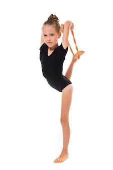Mädchen, das gymnastik in einem sportbadeanzug auf einem weiß mit kopienraum tut
