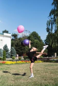 Mädchen, das gymnastik mit ballonen tut