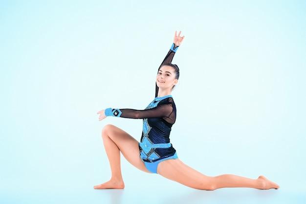 Mädchen, das gymnastik tanzt auf blau