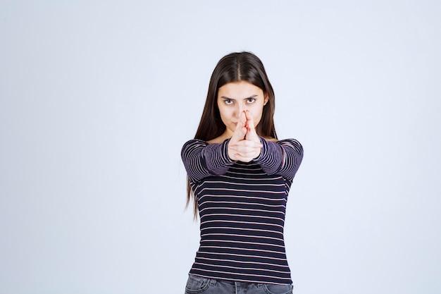 Mädchen, das handgewehrzeichen hält.