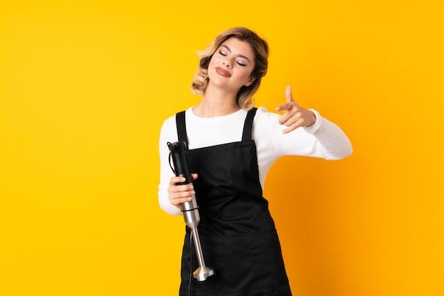 Mädchen, das handmixer lokalisiert auf gelber zeigender front mit glücklichem ausdruck verwendet
