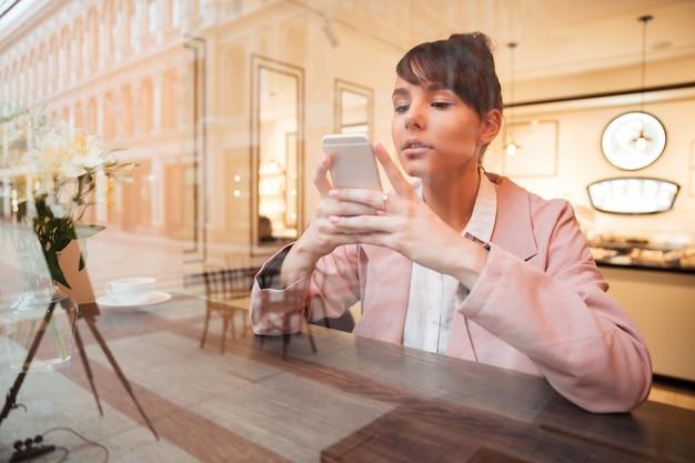 Mädchen, das handy beim sitzen am kaffeetisch benutzt