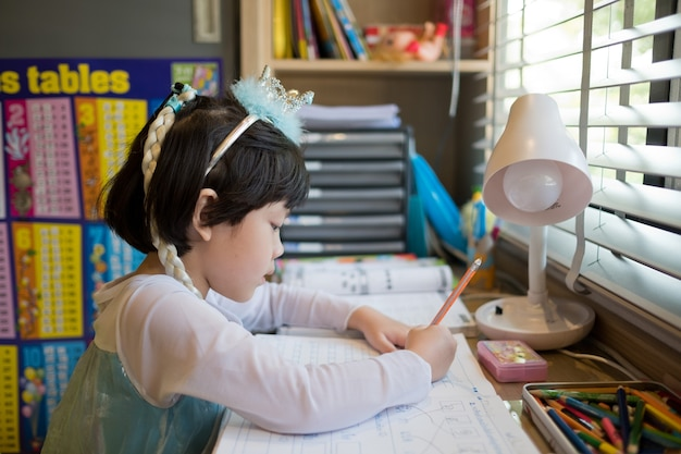 Mädchen, das hausaufgaben macht, kind, das papierbildungskonzept zurück zur schule schreibt