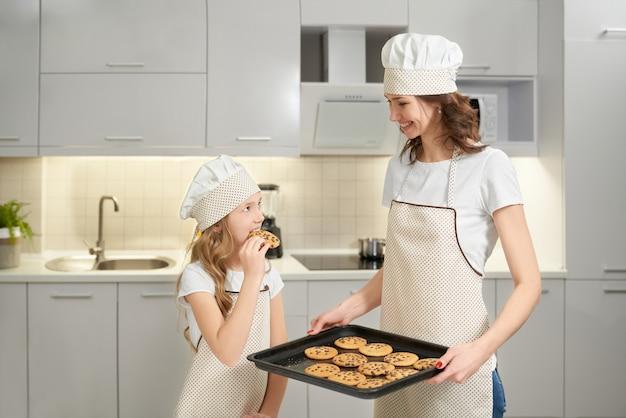Mädchen, das hausgemachte amerikanische kekse schmeckt, die von mutter gekocht werden.