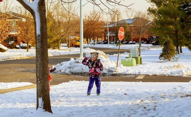 Mädchen, das herum draußen in den winter, spielend mit schnee geht