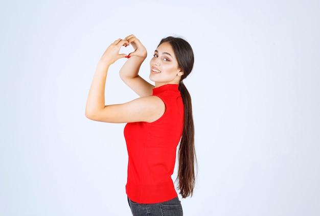Mädchen, das herzzeichen in der hand macht und liebe sendet.