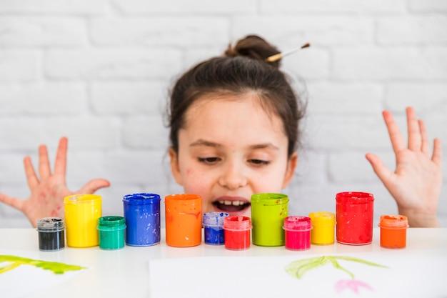 Mädchen, das hinter der tabelle steht und bunte farbenflaschen betrachtet