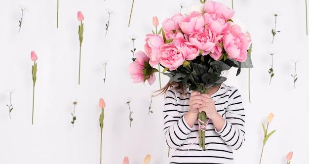 Mädchen, das hinter rosafarbenem blumenstrauß sich versteckt
