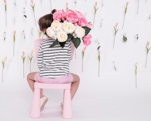 Mädchen, das hintere ansicht des rosafarbenen blumenstraußes hält