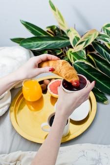Mädchen, das hörnchen am frühstück im raum, hotelservice isst. kaffee, marmelade, croissant, orangensaft, grapefruit, litschi.