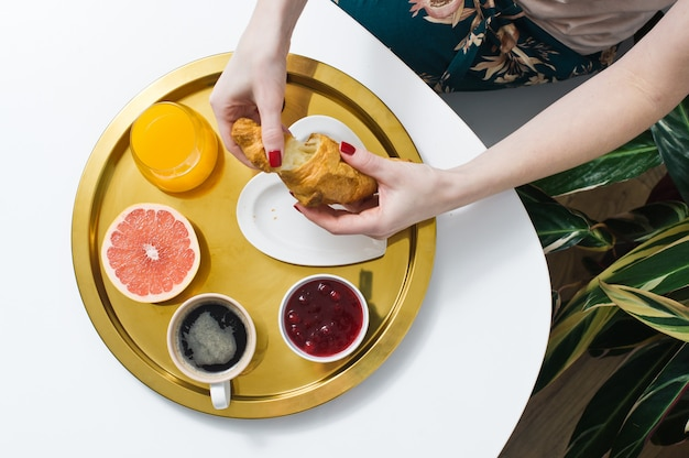 Mädchen, das hörnchen am frühstück isst. kaffee, marmelade, croissant, orangensaft, grapefruit, litschi.